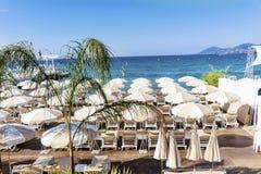 Взгляд пляжа на Канн с стульями и парасолями на белом песчаном пляже Стоковые Изображения
