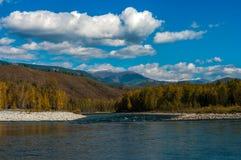 Взгляд реки и холмов с каменистым берегом Стоковые Изображения