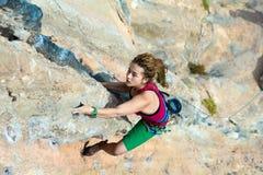 Взгляд сверху альпиниста утеса девушки вися высоко на скалистой стене Стоковая Фотография