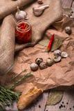 Взгляд сверху банка горячих красных перцев, пряного чеснока, яичек триперсток и розмаринового масла на скомканной бумажной и дере Стоковое Фото