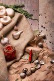 Взгляд сверху банка горячих красных перцев, пряного чеснока, яичек триперсток и розмаринового масла на скомканной бумажной и дере Стоковые Фото