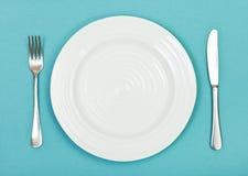 Взгляд сверху белой плиты, вилки, ножа на зеленом цвете Стоковые Фото