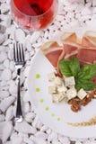 Взгляд сверху белой плиты вполне balyk, сыра и базилика и рюмки Деликатес на белых камнях Стоковое фото RF