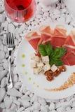 Взгляд сверху белой плиты вполне balyk, сыра и базилика и рюмки Деликатес на белых камнях Стоковая Фотография