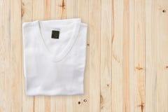 Взгляд сверху белой футболки на деревянной предпосылке таблицы Стоковые Изображения