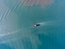 Взгляд сверху буксира движения на лазурной воде с пятном масла Стоковая Фотография