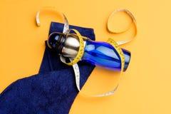 Взгляд сверху бутылки воды, измеряя ленты и полотенца изолированных на желтом цвете Стоковые Изображения RF