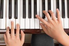 Взгляд сверху близкое вверх женских рук играя рояль стоковые изображения