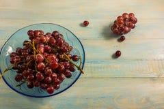 Взгляд сверху виноградины в стеклянном блюде на деревянной таблице Стоковое фото RF
