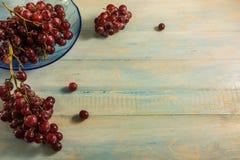 Взгляд сверху виноградины в стеклянном блюде на деревянной таблице Стоковые Фото