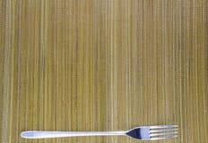 Взгляд сверху вилки и циновки на белой предпосылке Стоковые Фото
