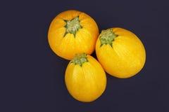 Взгляд сверху 3 всего и круглых желтых цукини на фиолетовой предпосылке Органические овощи для здоровых салатов Стоковая Фотография RF