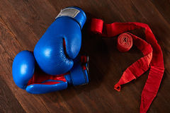 Взгляд сверху голубых и красных перчаток и повязки бокса на деревянной предпосылке планки Стоковые Изображения