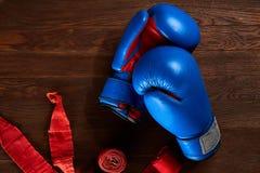 Взгляд сверху голубых и красных перчаток и повязки бокса на деревянной предпосылке планки Стоковые Фото