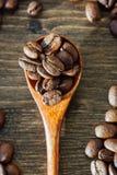 Взгляд сверху деревянной чайной ложки заполнило при кофейные зерна округленные с семенами кофе над предпосылкой woodeen Стоковые Фотографии RF