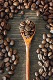 Взгляд сверху деревянной чайной ложки заполнило при кофейные зерна округленные с семенами кофе над предпосылкой woodeen Стоковая Фотография RF