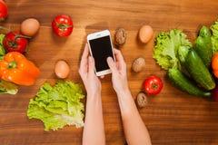 Взгляд сверху женщины держа мобильный телефон на кухонном столе стоковое изображение