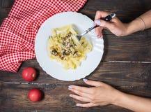 Взгляд сверху женщины есть макаронные изделия с грибами на деревянной таблице Стоковые Фотографии RF