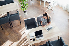 Взгляд сверху женщины используя ее компьтер-книжку на кафе Надземная съемка молодой женщины сидя на таблице с чашкой кофе и Стоковые Изображения RF