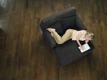 Взгляд сверху женщины используя компьтер-книжку на софе Стоковые Изображения