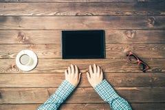 Взгляд сверху женщины сидя на деревянном столе при сложенные руки Стоковое Фото