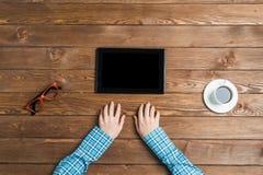 Взгляд сверху женщины сидя на деревянном столе при сложенные руки Стоковое фото RF