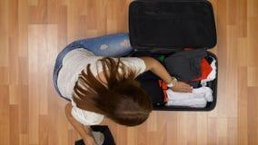 Взгляд сверху женщины спеша для того чтобы упаковать одежды в сумку вагонетки и выходя для того чтобы уловить полет акции видеоматериалы