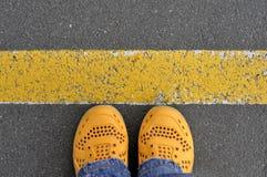 Взгляд сверху желтых ботинок на дороге асфальта с желтой линией Стоковые Изображения RF