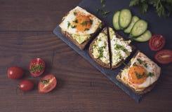 Взгляд сверху завтрака здравицы авокадоа здоровое Домодельный сандвич с авокадоом и яичницами, томатом вишни и огурцами на деревя Стоковое Фото