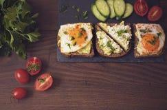 Взгляд сверху завтрака здравицы авокадоа здоровое Домодельный сандвич с авокадоом и яичницами, томатом вишни и огурцами на деревя Стоковые Фото