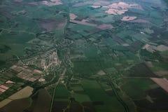 Взгляд сверху земли, зеленых полей с дорогами, взгляда от окна самолета Стоковые Фото