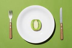 Взгляд сверху зеленого кивиа на белой плите с ножом и вилки на gre Стоковое фото RF