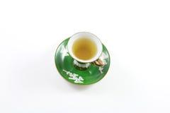 Взгляд сверху зеленых и белых чашка и поддонника с чаем стоковые фото