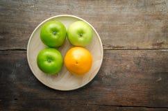 Взгляд сверху зеленых яблок и апельсина на деревянной плите, плодоовощах на w Стоковое Изображение RF