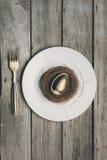 Взгляд сверху золотого пасхального яйца в гнезде на белой плите и вилке на деревянном столе, Стоковое Фото