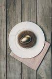 Взгляд сверху золотого пасхального яйца в гнезде на белой плите и салфетке на деревянном столе Стоковое Изображение RF