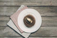 Взгляд сверху золотого пасхального яйца в гнезде на белой плите и салфетках на деревянном столе Стоковые Изображения