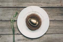Взгляд сверху золотого пасхального яйца в гнезде на белой плите на деревянном столе, Стоковая Фотография RF