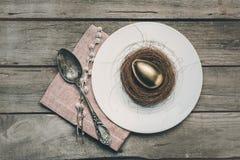 Взгляд сверху золотого пасхального яйца в гнезде на белой плите, салфетке, catkins и винтажной ложке на деревянном столе Стоковая Фотография RF