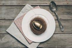 Взгляд сверху золотого пасхального яйца в гнезде на белой плите, салфетках и винтажной ложке на деревянном столе Стоковые Фотографии RF
