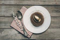 Взгляд сверху золотого пасхального яйца в гнезде на белой плите, салфетке, catkins и винтажной ложке Стоковое Фото