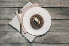 Взгляд сверху золотого пасхального яйца в гнезде на белых плите, вилке и салфетках на деревянном столе, Стоковое Фото