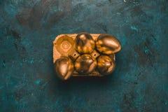 Взгляд сверху золотого цыпленка eggs в коробке яичка на столешнице Стоковая Фотография RF