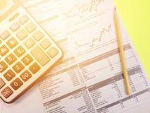 Взгляд сверху диаграмм данным по калькулятора, карандаша и компании общих на желтой предпосылке Стоковые Фото