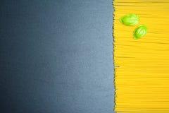 Взгляд сверху: итальянские макаронные изделия или спагетти на черной предпосылке шифера скопируйте космос Пустой шаблон еды Стоковое Изображение RF