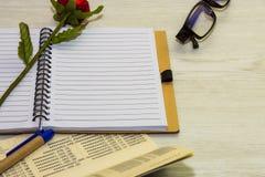 Взгляд сверху книги и ручки с стеклами на белой деревянной предпосылке Стоковое Изображение RF