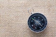 Взгляд сверху компаса на предпосылке холста мешковины стоковая фотография