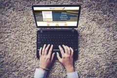 Взгляд сверху компьтер-книжки с вебсайтом недвижимости в экране Руки над клавиатурой Стоковое фото RF