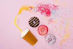 Взгляд сверху кофейной чашки и разнообразия заморозило donuts на пинке Стоковые Изображения