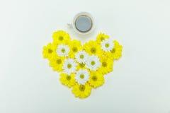 Взгляд сверху красивой белой и желтой хризантемы цветет в форме и чашке кофе сердца Стоковые Фото